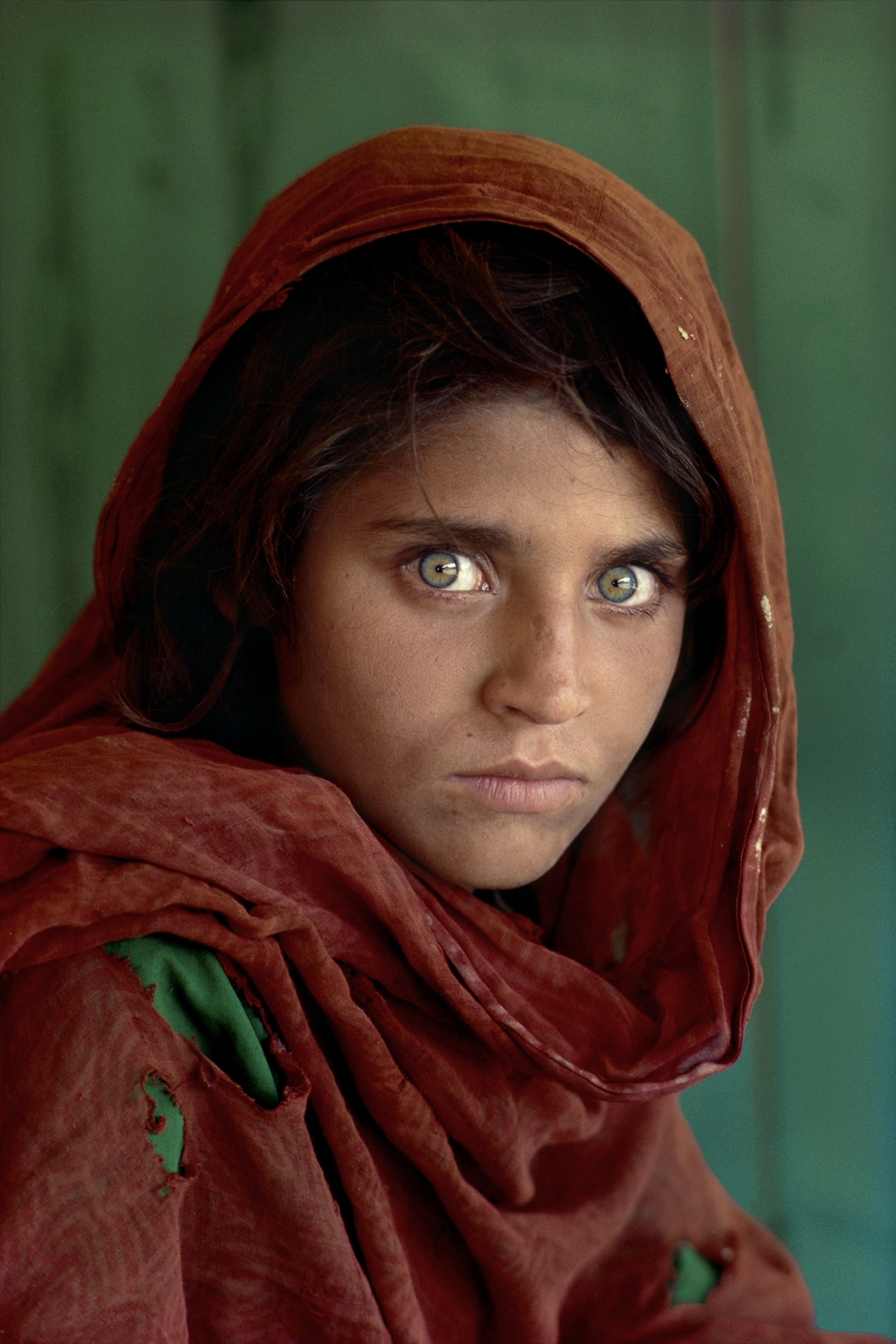 """Sharbat Gula, Afghan Girl, at Nasir Bagh refugee camp near Peshawar, Pakistan, 1984. National Geographic. """"The green-eyed Afghan girl became a symbol in the late twentieth century of strength in the face of hardship.  Her tattered robe and dirt-smudged face have summoned compassion from around the world;  and her beauty has been unforgettable.  The clear, strong green of her eyes encouraged a bridge between her world and the West.  And likely more than any other image, hers has served as an international emblem for the difficult era and a troubled nation."""" - Phaidon 55 The iconic image does not stand outside of time.  Rather, it connects with the moment in a deeply profound way.  Such as images are imbued with meaning, a significance that resonates deeply with a wide and diverse audience.  McCurry's photograph of the Afghan girl is one such image.  For many, this beautiful girl dressed in a ragged robe became a worldwide symbol for a nation in a state of collapse.   Bannon, Anthony. (2005). Steve McCurry. New York: Phaidon Press Inc., 12. NYC5958, MCS1985002 K035 Afghan Girl: Found National Geographic, April 2002 Iconic Photographs National Geographic Magazine, Along Afghanistan's War-torn Frontier, June 1985, Vol. 167, No. 6"""