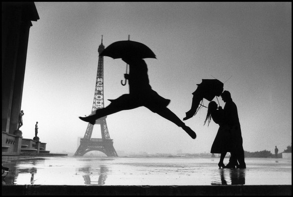 Elliott Erwitt Man with umbrella jumping over puddle in front of the Eiffel tower