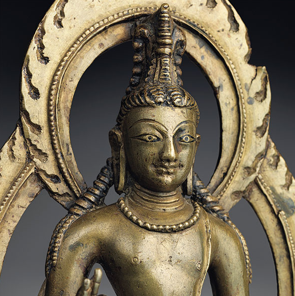 A BRONZE FIGURE OF MAITREYA KASHMIR OR WESTERN TIBET, CIRCA 1025 Superbly and elegantly cast standing in tribhanga on a lotus-base set on a stepped throne with an inscription at center, his right hand raised in vitarkamudra and holding a mala while grasping his water pot in his lowered left hand, clad in a diaphanous dhoti secured with a beaded double-belt, adorned with a beaded necklace, sacred thread and scarf draped over his elbows, his face with elongated almond-shaped eyes, incised eyebrows and faintly smiling lips, his hair pulled back into a high chignon fronted by a stupa and with thick locks escaping over his shoulders, backed by a beaded and flaming double-mandorla 12 ½ in. (31.7 cm.) high Estimate (Set Currency) $200,000 – $300,000 SAVE AS INTEREST FOLLOW PLACE BID Sale Information SALE 12255 — THE LAHIRI COLLECTION: INDIAN AND HIMALAYAN ART, ANCIENT AND MODERN 15 March 2016 New York, Rockefeller Plaza