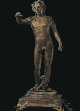 AN IMPORTANT LARGE ROMAN INLAID BRONZE BACCHUS CIRCA 2ND CENTURY A.D. The youthful god depicted nude, standing with his weight on his left leg, the right relaxed and bent at the knee, his left arm lowered, perhaps once holding a kantharos, and his right arm raised, perhaps once holding a cluster of grapes, his fleshy torso with copper inlays for the nipples, his head turned to his right, with a smooth forehead and modeled angular brows merging with the bridge of his nose, the lidded convex eyes inlaid in silver and articulated, his long hair center parted and bound in a copper fillet incised with a scrolling vine, with separately-made wavy tresses falling along his neck and spreading onto his shoulders, atop the original, elaborate, tiered plinth together with a seated panther at his feet, its left forepaw raised, the upper tier of the plinth circular in form with a cyma reversa molding, the lower square, with incised petals on the upper surface, a foliate band on the outer edge, a dog-tooth molding below, the corners supported by down-turned felines, their tails looped, their heads raised 33 5/8 in. (63.3 cm.) high Estimate (Set Currency) $500,000 – $700,000