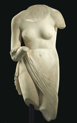 A ROMAN MARBLE VENUS CIRCA 1ST CENTURY B.C.-1ST CENTURY A.D. Lifesized, the voluptuous goddess depicted nude, standing with her left leg slightly advanced, her torso leaning forward causing a crease across her abdomen, both arms lowered, with a diaphanous mantle draped diagonally across her legs and over the crook of her right arm, with folds cascading down her upper right thigh 35 ½ in. (90.2 cm.) high Estimate (Set Currency) $300,000 – $500,000