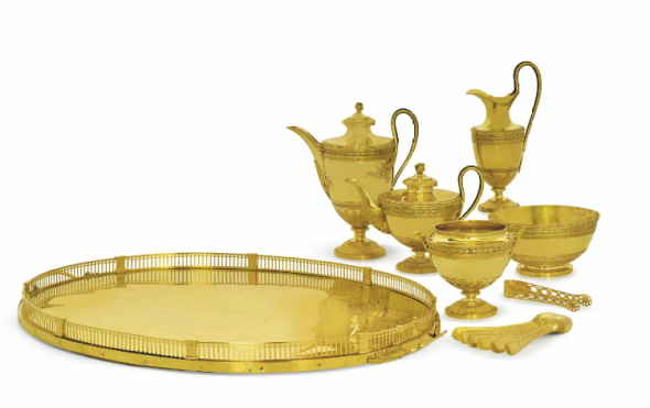A RUSSIAN TWO-COLOR GOLD TEA AND COFFEE-SERVICE MARK OF IWAR WENFELDT BUCH, ST. PETERSBURG, 1799, ASSAY MASTER'S MARK OF ALEXANDER YASHINOV, 82 ZOLOTNIK (20½ kt.) STANDARD MARK, THE TEASPOONS AND SUGAR-TONGS UNMARKED Comprising vase-shaped teapot, coffee-pot, milk-jug, two-handled sugar-bowl and waste-bowl, each on circular domed base chased with beading and vertical leaves, the lower part of the body with foliage calyx and bead and foliage bands, the border with similar bands and green-gold laurel between plain ribs, the teapot and coffee-pot with acanthus leaf spouts, the bifurcated handles inset with bone and terminating in acanthus foliage, the waisted covers with foliage borders and acanthus bud finials, each marked on foot, an oval two-handled tray, the gallery in sections with plain pilasters at intervals, pierced with vertical slats and arcading and with beaded rim, the loop handles terminating in laurel foliage and engraved with bright-cut ornament between wriggle-work borders, marked under one handle, six teaspoons with wriggle-work stems partly chased with foliage and a pair of sugar-tongs, the similar stems pierced and chased with flower-heads, the pierced grips and join with patera (13) the coffee-pot 10 ½ in. (26.7 cm) high, the tray 25 ½ in. (64.7 cm) long total gross weight excluding the wood support to the tray 239 oz. (7,433 gr.)Estimate (Set Currency) $1,500,000 – $2,500,000