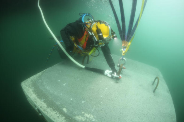 A diver connects a rope made of ultra-high-molecular-weight polyethylene (UHMWPE), covered with a polyester protective layer with a breaking load of 20 metric tons, to one of the anchors on the lakebed to keep the piers in place, March 2016 Photo: Wolfgang Volz