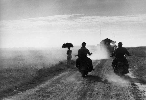 Motorcyclists and woman walking on the road from Nam Dinh to Thai Binh, Vietnam, May 25, 1954 © Robert Capa © International Center of Photography/Magnum Photos