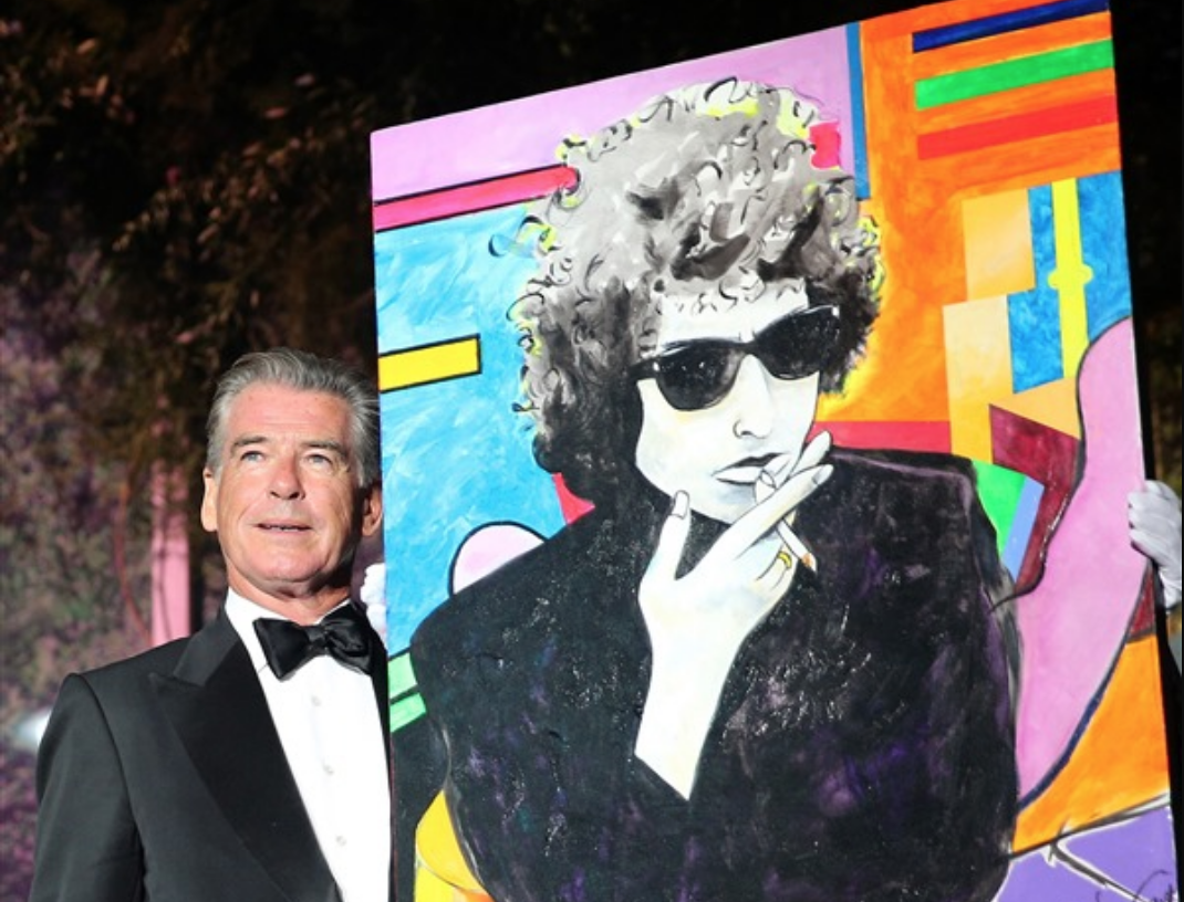Pierce Brosnan with his $1.4 million painting of Bob Dylan. Photo courtesy of amFAR.