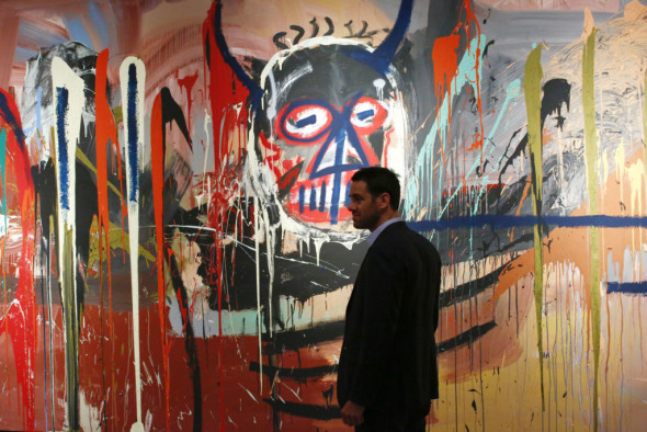 Loic Gouzer Deputy Chairman, Post-War and Contemporary at Christie's stands next to the artwork 'Untitled' made by artist Jean-Michel Basquiat on April 29, 2016 during a press preview of Christie's forthcoming evening auctions of the Contemporary, Impressionist, Modern and Post-War Art in New York. As part of the 20th Century season in New York, the Post-War and Contemporary Art Evening Sale takes place on 12 May, featuring some of the leading modern masters and contemporary stars of today. / AFP / KENA BETANCUR / RESTRICTED TO EDITORIAL USE - MANDATORY MENTION OF THE ARTIST UPON PUBLICATION - TO ILLUSTRATE THE EVENT AS SPECIFIED IN THE CAPTION        (Photo credit should read KENA BETANCUR/AFP/Getty Images)