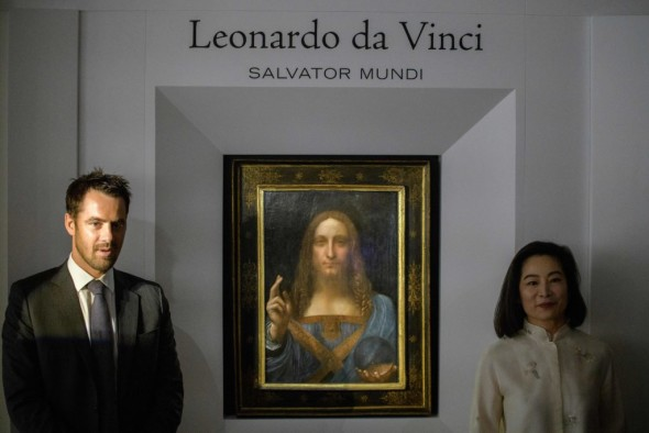 Christies representatives pose after Leonardo da Vinci's 'Salvator Mundi' painting was unveiled in Hong Kong on October 13, 2017.  / AFP PHOTO / Anthony WALLACE / RESTRICTED TO EDITORIAL USE - MANDATORY MENTION OF THE ARTIST UPON PUBLICATION - TO ILLUSTRATE THE EVENT AS SPECIFIED IN THE CAPTION        (Photo credit should read ANTHONY WALLACE/AFP/Getty Images)