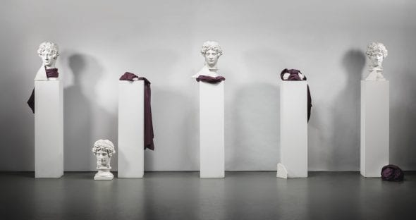 Giulio Paolini LA CASA DI LUCREZIO FOUR WHOLE AND ONE FRACTURED PLASTER CASTS, FABRICS, FRAGMENTS OF CARVED PLASTER TABLET, WHITE PLINTHS. EXECUTED IN 1981. OVERALL DIMENSIONS VARIABLE. THIS WORK IS REGISTERED AT THE FONDAZIONE GIULIO E ANNA PAOLINI, TURIN, UNDER THE N. GPO-0455 Estimate 250,000 — 350,000 EUR